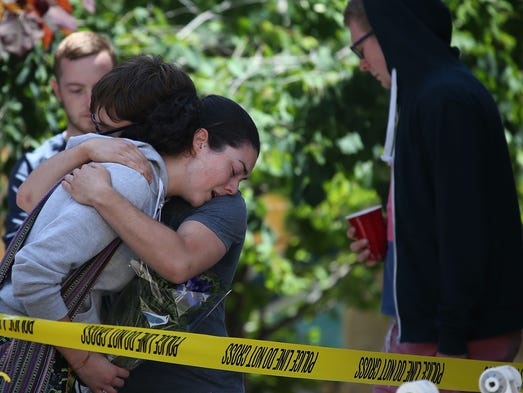 A woman cries as she leaves flowers at the scene of