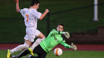 Churchville-Chili's Lukas Fernandes, left, slips past Rush-Henrietta goalie Alex Paratore for a second-half goal on Tuesday. Fernandes also had three assists in the Saints' 5-2 win.