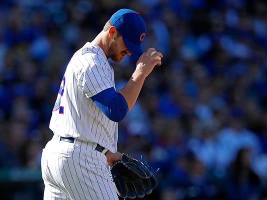 FILE - In this Sept. 9, 2017, file photo, Chicago Cubs' Justin Grimm adjusts his cap after being called for a balk during the third inning of a baseball game against the Milwaukee Brewers in Chicago. Grimm lost his arbitration hearing against the Cubs. Grimm was given a pay hike from $1,825,000 to $2.2 million on Thursday, Feb. 8, 2018, by Mark Burstein, Gary Kendellen and James Darby. He had asked for $2,475,000. (AP Photo/Jim Young, File)