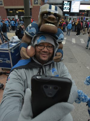 Alejandro McClain of Detroit but now living in Maryland, takes a selfie in front of Ford Field before Sunday Night Football.