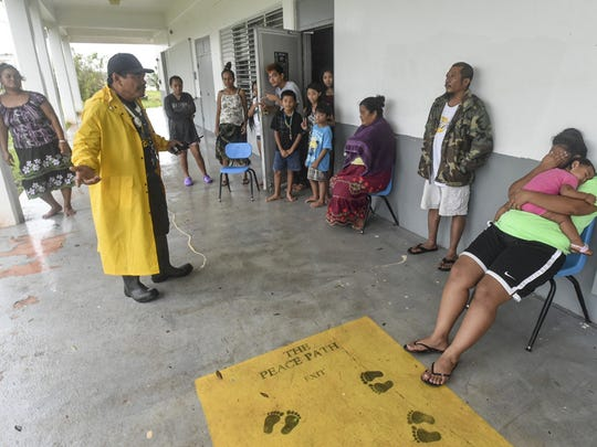 Astumbo Elementary aide Joseph Cruz, wearing rainjacket, gives instructions to shelter residents to return home and assess damage to their houses following Typhoon Dolphin on May 16.  Residents would be allowed to stay at the shelter if their homes were destroyed, accoring to shelter manager Angel Legaspi.