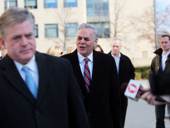 Attorney Michael Burke, left, leads the way for his