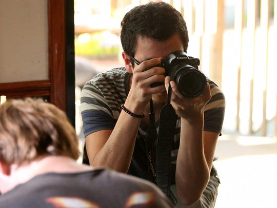 Jake Ortega takes photographs at Coffee Oasis in Port