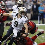 New Orleans Saints quarterback Drew Brees (9) is dragged down as he scrambles in the first half of Sunday's game.