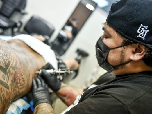 Master tattoo artist and owner Art Root works on a
