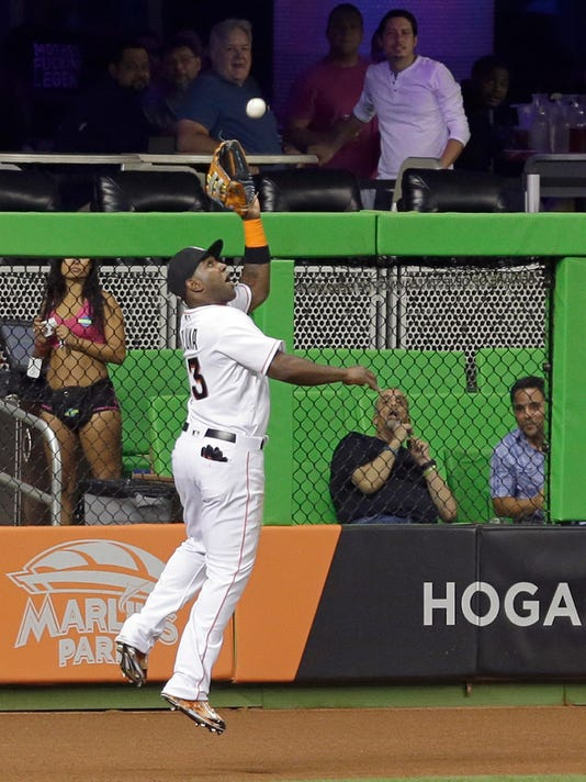 Miami Marlins left fielder Marcell Ozuna catches a fly ball by Washington Nationals' Trea Turner in the first inning of a baseball game, Wednesday, Sept. 21, 2016, in Miami. (AP Photo/Alan Diaz)