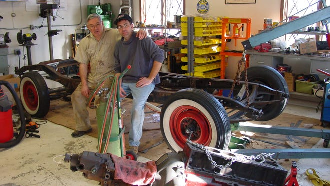 Ed Brune, left, and son John Brune take a break to pose while restoring the father's 1936 Chevrolet Master Deluxe Coupe, which he bought for $150 at age 15.