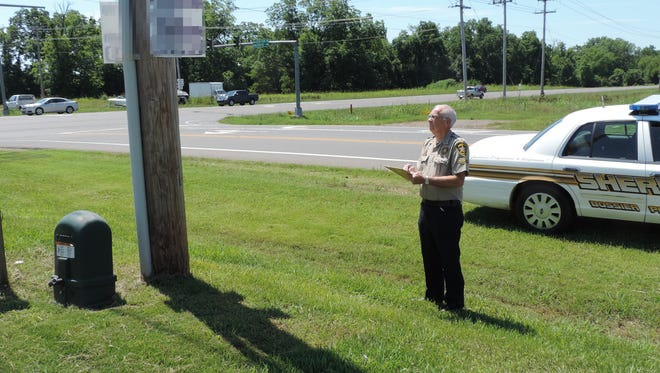 Bossier Sheriff's Office Posse member, Mel Allen, records information from a sign located on a utility pole, at the intersection of Airline Dr. and Kingston Rd., in north Bossier Parish.