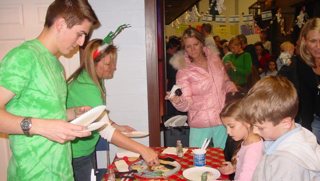 Michael Susenjer and Stephanie Enos of Martin County help guests decorate their own cookies for Santa at The Children's Museum of the Treasure Coast Holiday's Around the World.