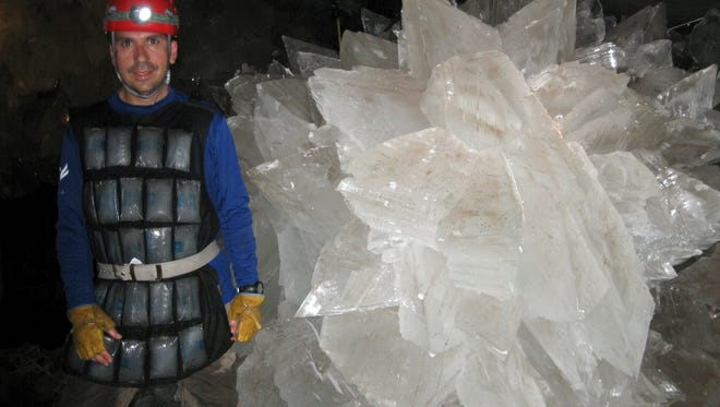 In this image provided by Mike Spilde, Mario Corsalini stands near to a gypsum rosette crystal. In a Mexican cave system so beautiful and hot that it is called both Fairyland and hell, scientists have discovered life trapped in crystals that could be 50,000 years old. The bizarre and ancient microbes were found dormant in caves in Naica, Mexico, and were able to exist by living on minerals such as iron and manganese, said Penelope Boston, head of NASA's Astrobiology Institute.