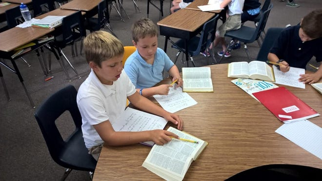 St. Gabriel Elementary School, Neenah, third-grade students frequently spend time studying the Bible. Students learned how to find a Bible citation together for the previous Sunday's gospel. Pictured are Max Vosters and Meryk Larson.