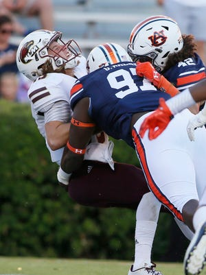 Auburn lineman Andrew Williams (79) and linebacker Tre' Threat (42) tackle ULM quarterback Garrett Smith (13) in the end zone for a safety during the fourth quarter at Jordan Hare Stadium.