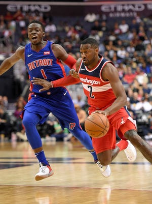 Wizards guard John Wall dribbles past Pistons guard Reggie Jackson in the second half Friday, Oct. 20, 2017, in Washington.