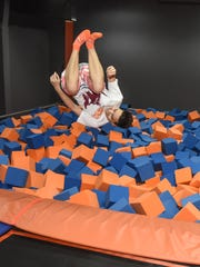 Children jump and flip off stretched out material of