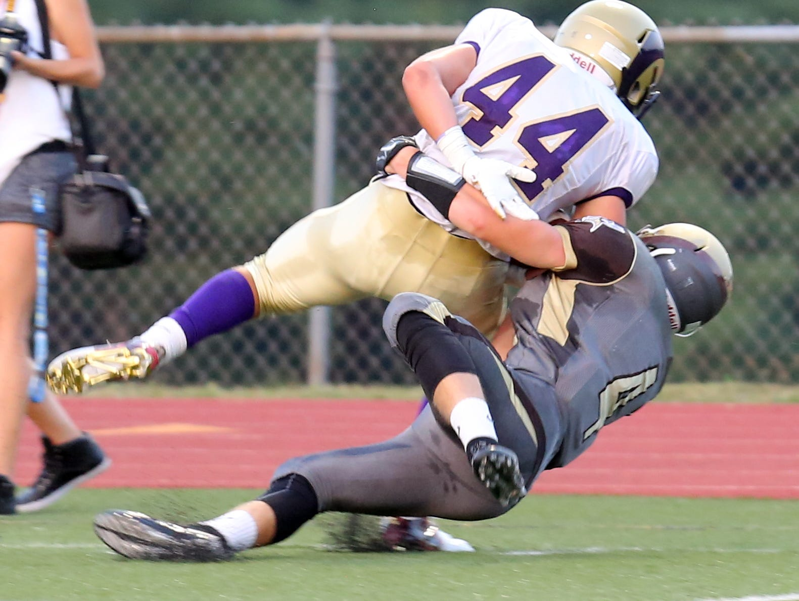 Clarkstown South's Kyle Samuels (4) tackles Clarkstown North's Michael Porco (44) during game action at Clarkstown South High School in West Nyack Sept. 4, 2015.