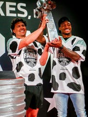 Farmer JJ Nunes, left, and Minnesota Vikings wide receiver Stefon Diggs hoist the trophy for winning the Land O'Lakes Farm Bowl on Thursday, Feb. 1, 2018 in Minneapolis.