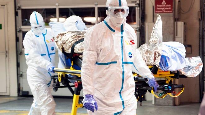 Cuban doctor Felix Baez Sarria, who contracted Ebola in Sierra Leone, arrives on a gurney at the Geneva University Hospital in Geneva, Switzerland, Friday, Nov. 21, 2014.