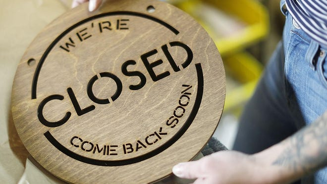"""A laser-cut """"closed"""" sign for a business."""