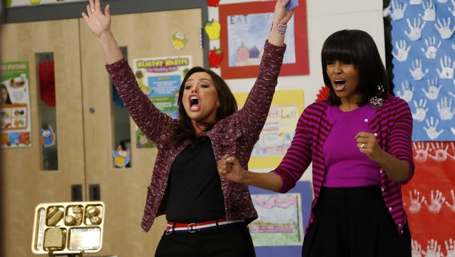 First lady Michelle Obama, seen here in 2013 with celebrity chef Rachael Ray cheering on students from Eastside and Northside Elementary schools as part of the Get Fit Let's Move! program in Clinton, made fighting childhood obesity the focus of her time in the White House.