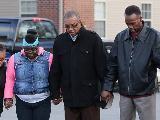 Ronald Benton, second from the right, leads the group in prayer before an anti-crime march at the East Pointe Apartment Complex on Friday, Feb. 5, 2016. Benton is a pastor at Mount Moriah Missionary Baptist Church.