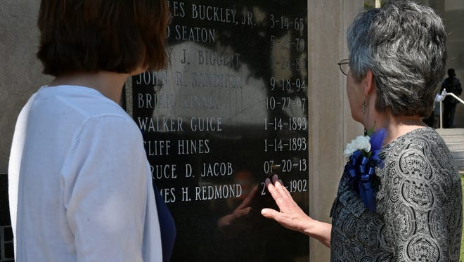 Rhonda Redmond, right, views the newly etched named of her great-grandfather JPD officer James Redmond at the Jackson Police Department Fallen Officer Memorial in Downtown Jackson on Thursday. Officer James Redmond died in the line of duty in 1902, and after a century his name was added to the Fallen Officer Memorial at JPD headquarters. At left, James Redmond's great-great-granddaughter Hannah Knowles.