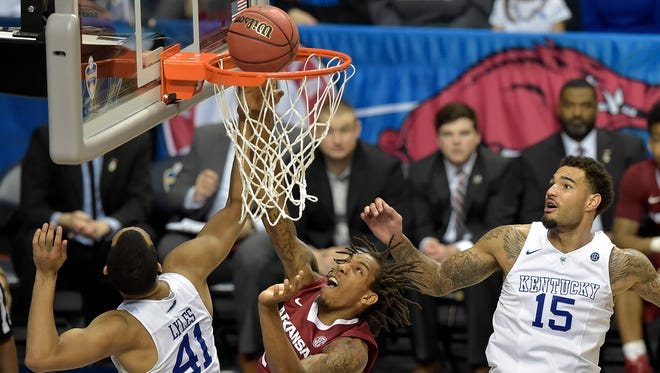 Arkansas guard Michael Qualls (24) shoots as Kentucky forward Trey Lyles (41) and Kentucky forward Willie Cauley-Stein (15) look on during the second half of the NCAA college basketball Southeastern Conference tournament championship game, Sunday, March 15, 2015, in Nashville, Tenn. Kentucky won 78-63. (AP Photo/Mike Stewart)