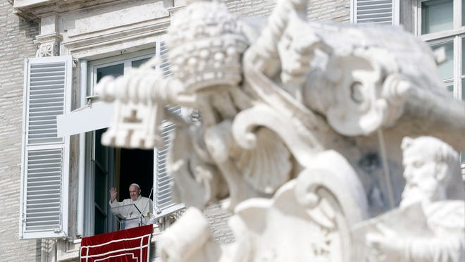 Pope Francis waves during the Angelus noon prayer delivered from his studio window overlooking St. Peter's Square, at the Vatican, on Sunday in Rome.