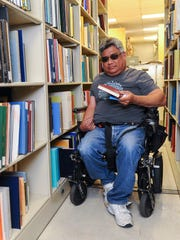 Library technician Francis Dadufalza, 48, locates a book requested from the resource library in the Richard Flores Taitano Micronesian Area Research Center at the University of Guam in Mangilao on Friday, June 10.