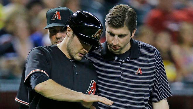 Arizona Diamondbacks center fielder A.J. Pollock (11reacts after being hit by a pitch by  Cincinnati Reds starting pitcher Johnny Cueto (47) in the 8th inning of their MLB game Saturday, May 31, 2014 in Phoenix, Ariz.