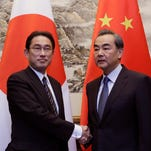 Japanese Foreign Minister Fumio Kishida, left, shakes hands with China's Foreign Minister Wang Yi during a meeting at Diaoyutai State Guesthouse, in Beijing, China,  on April 30, 2016.