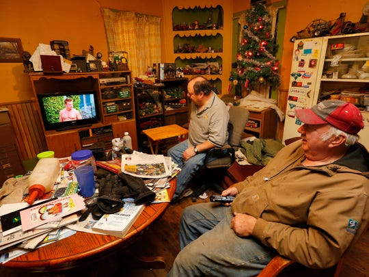 """Bob Anderson, 54, and his brother Roy, 70, watch """"The Bachelor"""" at their farm near Brighton on Jan. 12. """"I wonder if he's got grease under his fingernails,"""" Roy said of Iowa's Chris Soules."""