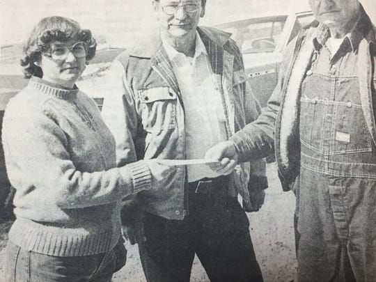 Nyra Duncan, left, with the Uniontown Jayceettes, accepted a $600 check from Dick Blanford. The $600 was what Ed Buckman, center, of Smith Mills bid to purchase a heifer at an auction held at Blanford's Smith Mills farm in March 1984.