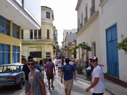 Peter Loch, left, and Eli Cate, right, walk down a side alley in Old Havana, Cuba, with members of their Michigan-based youth baseball team on Aug. 3, 2017.