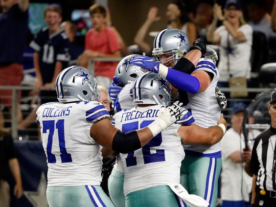 Dallas Cowboys' La'el Collins (71) and Travis Frederick (72) celebrate with Jason Witten, top right, after Witten caught a touchdown pass in the first half of an NFL football game against the New York Giants on Sunday, Sept. 10, 2017, in Arlington, Texas.