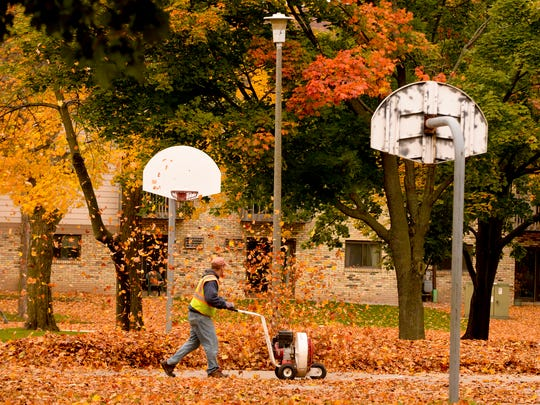 FILE - Jack Ploederl, from the city of Manitowoc Parks and Recreation Department, uses an eight-horse walk-behind blower to clear fallen autumn leaves from Washington Park in Manitowoc on Oct. 20, 2014.