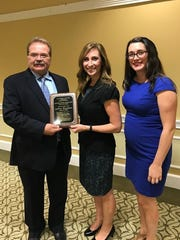 Jeffrey Barnhart, left, president-CEO of Creative Marketing Alliance, is pictured with Tana Smith, center, principal, Hopewell Valley Central High School, and Erin Klebaur, director of marketing services at Creative Marketing Alliance, after he was introduced as a Distinguished Graduate of the high school.