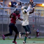 Lincoln defender Raeckwon Archer makes an interception in front Shane Sanders as the Lincoln High Trojans cruised past the Chiles Timberwolves on Friday at Cox Stadium.