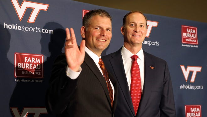 Incoming Virginia Tech head football coach Justin Fuente, left, waves during  a news conference Monday after he was formally announced as Virginia Tech's next head football coach by athletic director Whit Babcock, right, in Blacksburg,