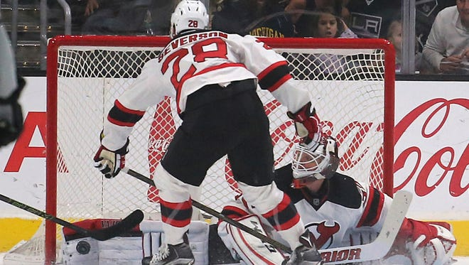 New Jersey Devils goalie Cory Schneider (35) blocks a Los Angeles Kings shot on goal as defenseman Damon Severson (28) protects in the first period of an NHL hockey game in Los Angeles Saturday, Nov. 19, 2016.  (AP Photo/Reed Saxon)
