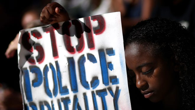 A demonstrator holds a sign during a moment of silence on August 14, 2014 in Oakland, Calif.