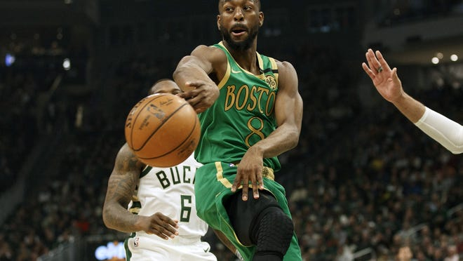Celtics guard Kemba Walker dishes against the Milwaukee Bucks during a game in January.