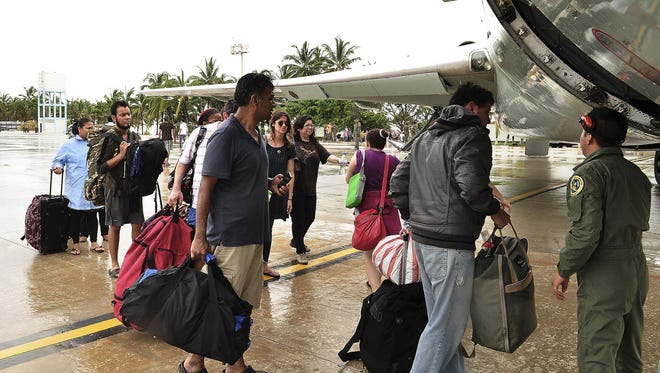 Tourists board a plane of the Mexican Air Force at the Pie de La Cuesta military base in Acapulco, Mexico, on Tuesday.