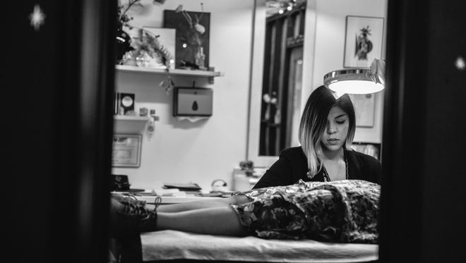 Hand-poke tattoo artist Taylor Elyse Compton completes a tattoo in her Yucca Valley studio.