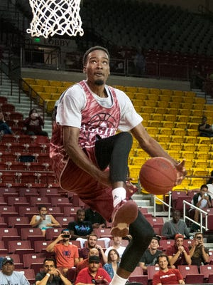New Mexico State's Jalyn Pennie takes an attempt at the through the legs dunk in a post game impromptu dunk contest after the Crimson and White Scrimmage Saturday night at the Pan American Center.