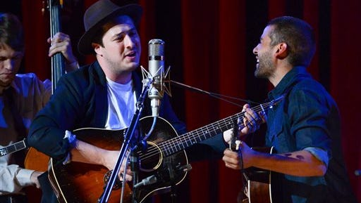 "FILE - In this Sept. 29, 2013 file photo, musicians Marcus Mumford, left, and Oscar Isaac perform together during ""Another Day, Another Time: Celebrating the Music of Inside Llewyn Davis"" at The Town Hall in New York. Fans of the Coen brothers' amused, affectionate portrait of the 1960s Greenwich Village folk scene _ and of banjo-playing, guitar-plucking Americana in general _ will relish this recording of a 2013 New York concert celebrating the music of the movie ""Inside Llewyn Davis."" (Photo by Evan Agostini/Invision/AP, File)"