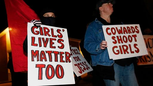Nazzi McDonnell, left, of Colorado Springs, Colo., joins other participants in waving placards during a vigil near the scene of the early morning fatal shooting of a young woman who hit and injured a Denver Police Department officer while driving a stolen vehicle Monday in northeast Denver.
