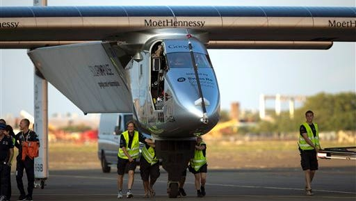 FILE - In this July 3, 2015, file photo, ground crew push the Solar Impulse 2, a solar powered airplane, towards the hangar after landingat the Kalaeloa Airport in Kapolei, Hawaii. The Solar Impulse team said in a news release early Wednesday, July 15, 2015, that they are suspending the around-the-world journey in Hawaii, after the plane suffered battery damage during its flight to the islands. The team will continue the attempt, but irreversible damage caused by overheating batteries has grounded the flight until at least April. (AP Photo/Marco Garcia, File)