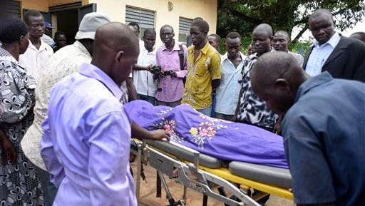 """Relatives and other mourners watch as the body of South Sudanese journalist Peter Julius Moi is taken into the mortuary in Juba, South Sudan Thursday, Aug. 20, 2015. The father of Moi, a reporter for the Corporate Weekly, says unknown gunmen shot his son twice in the back and killed him late Wednesday, Aug. 19, 2015 on the outskirts of the capital Juba, in an attack that came days after President Salva Kiir was reported to have threatened to kill reporters """"working against the country."""" (AP Photo/Jason Patinkin)"""