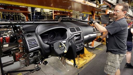 In this June 9, 2015, file photo, a Ford Motor Co. employee works on the instrument panel of a 2016 Ford Explorer at the Chicago Assembly Plant in Chicago. The Commerce Department says orders for durable goods increased 2 percent in July after a 4.1 percent gain in June.