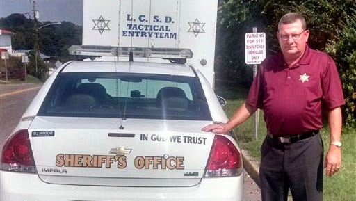 "Lee County, Va., Sheriff Gary Parsons stands next to a patrol car that displays an ""In God We Trust"" decal on Friday, Sept. 4, 2015. Parsons said his office spent a total of $50 to have the decals added to about 25 vehicles. He said many people feel their belief system is being trampled and that adding the phrase is a way of pushing back. But a watchdog group says the decals amount to an illegal government endorsement of religion."
